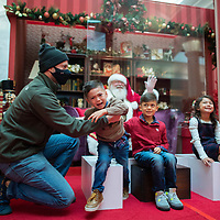 MOORESTOWN, NJ:  Derek Sanko, 3, screams while posing for portraits with Santa separated through plexiglass due to the coronavirus (COVID-19) pandemic at the Moorestown Mall in Moorestown, NJ on December 5, 2020. The pandemic has forced difficult decisions about maintaining the holiday tradition of visits to Santa Claus versus safety concerns.  Plexiglass dividers, face shields, and physical distancing are among the precautions for those locations that have proceeded with Santa photo opportunities.  CREDIT:  Mark Makela for The New York Times