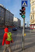 Beneath a pedestrian sign, a jaywalker steps out into the road on a red light and looking the wrong way in Holesovice district, Prague on 20th March, 2018, in Prague 7, the Czech Republic. Crossing the road very seriously in the Czech Republic and jaywalkers may be fined if they attempt to cross a road or tram tracks within 50 metres of a designated crossing point - a zebra style crossing or traffic lights. You may also be fined if you cross at a pedestrian crossing if the green pedestrian crossing light is not lit.