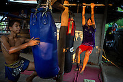 Phatsorn Bunmasen, 14, is lifting herself while training with another fighter at the gym where she practises Muay Thai boxing, in a village near Ubon Ratchathani, northeast Thailand.