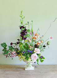 Charlie McCormick's flower arrangement<br /> Lily 'Tiger Babies', Rosa 'Aphrodite' and 'Pretty Jessica', black hollyhock (Alcea nigra), with edibles — redcurrants and globe artichokes, and trailers, honeysuckle and clematis over the sides of the vase. Cosmos 'Daydream', sweet peas 'Wiltshire Ripple' and 'Almost Black' and poppy seed heads, dried and fresh