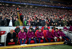 Manchester City manager Pep Guardiola (left), assistant coach Domenec Torrent (second left) and assistant coach Mikel Arteta (third left) in the dugout in front of Liverpool fans