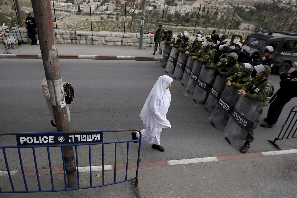 A Palestinian woman walks past Israeli border and anti-riot police officers moments before Palestinian Muslim worshippers started to perform the Friday prayers on the street, after they were denied entry to the Al Aqsa Mosque for security reasons, near east Jerusalem's Old City, on January 23, 2009. Israeli police restricted access to the Al-Aqsa mosque compound in Jerusalem to Palestinian men over 40 who had come to attend the first Friday sermon since a ceasefire halted the violence in the Gaza Strip.
