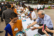 "23 APRIL 2013 - BANGKOK, THAILAND:   Thais place books donated to Thai literacy projects into monks' alms bowls during the opening ceremony to mark Bangkok as the World Book Capital City 2013. UNESCO awarded Bangkok the title. Bangkok is the 13th city to assume the title of ""World Book Capital"", taking over from Yerevan, Armenia. Bangkok Governor Suhumbhand Paribatra announced plans that the Bangkok Metropolitan Administration (BMA) intends to encourage reading among Thais. The BMA runs 37 public libraries in the city and has modernised 14 of them. It plans to build 10 more public libraries every year. Port Harcourt, Nigeria will be the next World Book Capital in 2014..PHOTO BY JACK KURTZ"