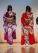 Women in kimonos bowing. Nishijin Textile Center regularly presents beautiful kimono fashion shows, in Kyoto, Japan.