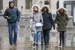 © Licensed to London News Pictures. 15/12/2018. London, UK. Tourists shelter under hoods during a wet, cold, blustery day in London. Photo credit: Dinendra Haria/LNP