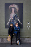 Two young woman listen to a busker beneath a portrait of the Countess-Duchess of Benavente by Francesco Goya (1885), work sponsored by Credit Suisse and advertised on a construction hoarding outside the National Portrait Gallery. In a scene about the ordinary girl's life in the 21st century versus that of an aristcratic woman. Doña María Josefa Alonso-Pimentel y Téllez-Girón, Duchess of Osuna, Grandee of Spain, suo jure 15th Countess-12th Duchess of Benavente, Grandee of Spain (1752 - 1834) was a Spanish aristocrat, famous for her patronage of artists, writers and scientists and who died at the age of 81.