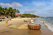 Beach scene, with a fisherman tending his nets and lines by his traditional coracle fishing boat (Thung chai). Mui Ne, Vietnam