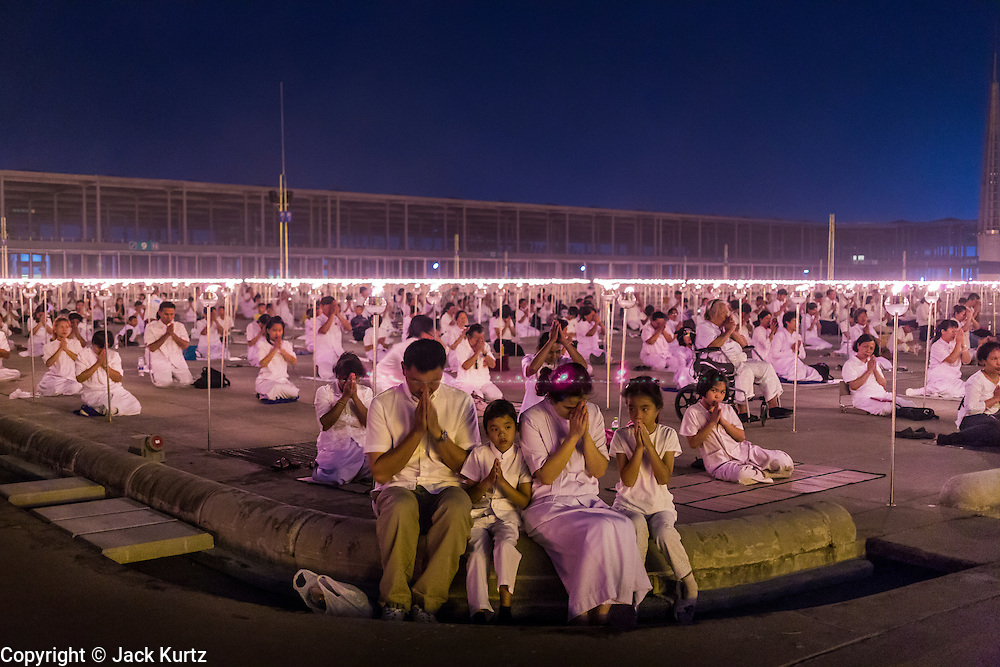 """14 FEBRUARY 2014 - KHLONG LUANG, PATHUM THANI, THAILAND: Lay people participate in the evening candle light procession for Makha Bucha Day at Wat Phra Dhammakaya. The aims of Makha Bucha Day are: not to commit any kind of sins, do only good and purify one's mind. It is a public holiday in Cambodia, Laos, Myanmar and Thailand. Many people go to the temple to perform merit-making activities on Makha Bucha Day. The day marks four important events in Buddhism, which happened nine months after the Enlightenment of the Buddha in northern India; 1,250 disciples came to see the Buddha that evening without being summoned, all of them were Arhantas, Enlightened Ones, and all were ordained by the Buddha himself. The Buddha gave those Arhantas the principles of Buddhism, called """"The ovadhapatimokha"""". Those principles are:  1) To cease from all evil, 2) To do what is good, 3) To cleanse one's mind. The Buddha delivered an important sermon on that day which laid down the principles of the Buddhist teachings. In Thailand, this teaching has been dubbed the """"Heart of Buddhism."""" Wat Phra Dhammakaya is the center of the Dhammakaya Movement, a Buddhist sect founded in the 1970s and led by Phra Dhammachayo.    PHOTO BY JACK KURTZ"""