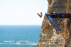 © Licensed to London News Pictures. 14/07/2019. Beirut, Lebanon. A competitor performs a dive during the Red Bull Cliff Diving elite competition on Raouche Rocks, Beirut, Lebanon. Beirut is the fifth location out of seven events on the world tour. Photo credit : Tom Nicholson/LNP
