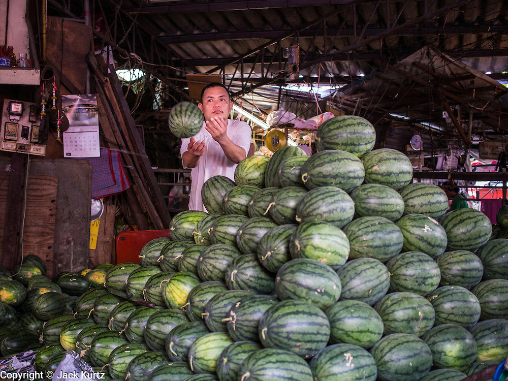 """03 APRIL 2014 - BANGKOK, THAILAND:    A vendor stacks watermelons in a stand in Khlong Toey Market. Khlong Toey (also called Khlong Toei) Market is one of the largest """"wet markets"""" in Thailand. The market is located in the midst of one of Bangkok's largest slum areas and close to the city's original deep water port. Thousands of people live in the neighboring slum area. Thousands more shop in the sprawling market for fresh fruits and vegetables as well meat, fish and poultry.     PHOTO BY JACK KURTZ"""