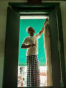 15 JULY 2015 - THONBURI, BANGKOK, THAILAND: A man hangs curtains in Bang Luang Masjid (Masjid is the Thai word for mosque). Located on the west bank of the Chao Phraya River and built in the reign of King Rama I (1782-1809), Bangluang Mosque is one of the oldest mosques in Bangkok and is unique because it's designed in a traditional Thai style and decorated with Thai, European, and Chinese art. The Mosque carries Islamic symbolic features such as 30 pillars, 12 windows and 1 door which represent the numbers of chapters in the Koran and the 13 regulations of Islamic worshipping ritual.    PHOTO BY JACK KURTZ