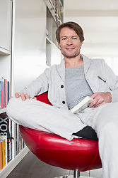 Portrait of mature man sitting on chair with book, smiling