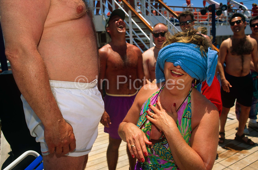 Whilst on a cruise aboard the Fun Ship Ecstasy during a voyage from Miami around the Gulf of Mexico, passengers enjoy a sexual game on deck beneath a strong tropical sun. Male contestants have lined up to be inspected by a blindfolded lady wearing a swim suit and painted nails who is required to identify her own husband by feeling his lower body and torso. Howls of laughter emit from the other men as the lady realises that this is indeed her own spouse who stands on a chair, his bulging crotch at chest height. She smiles to herself, still blind beneath a towel and the moment is funny enough for all to enjoy a happy hour of organised entertainment on deck. The Panamanian-registered MS Ecstasy is a 70,367 ton cruise ship carrying 2,052 passengers and 920 crew belonging to Vegas-style Carnival Cruise lines.