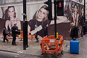 Roadworks disruption, passers-by and fashion retail models on construction hoarding in central London. Large images of women adorn the posters on the site screens and they look down on passers-by on London's Oxford Street in the borough of Westminster. Beneath the ladies are men going about their business: Either carrying retail shelving or wheeling a blue suitcase. It is a scene of gender, of sexuality and the urban everyday - amidst continuing roadworks.