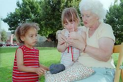 Grandmother teaching grandchildren how to knit,