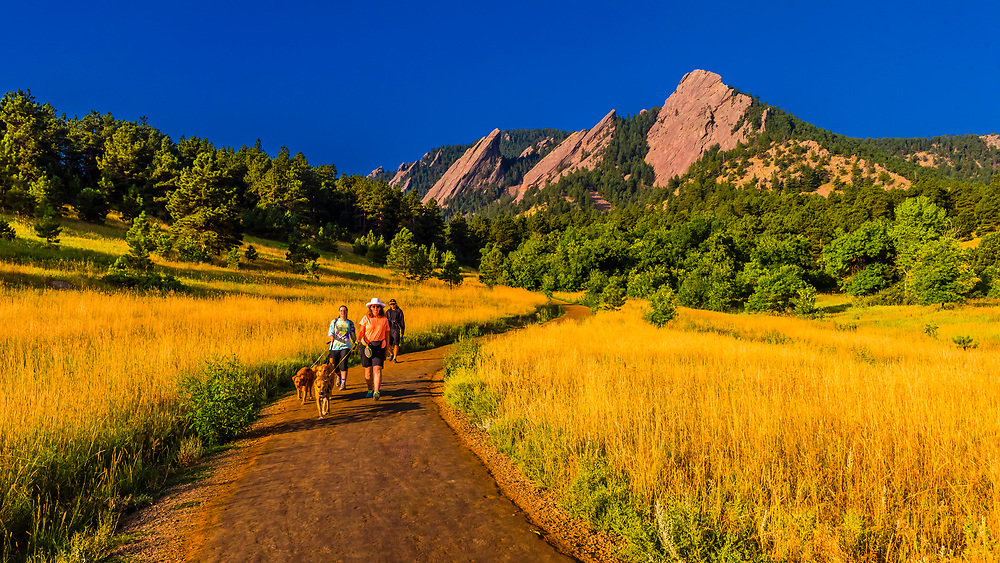 Hikers walking their dogs, The Flatirons rock formations, Chautauqua Park, Boulder, Colorado USA.