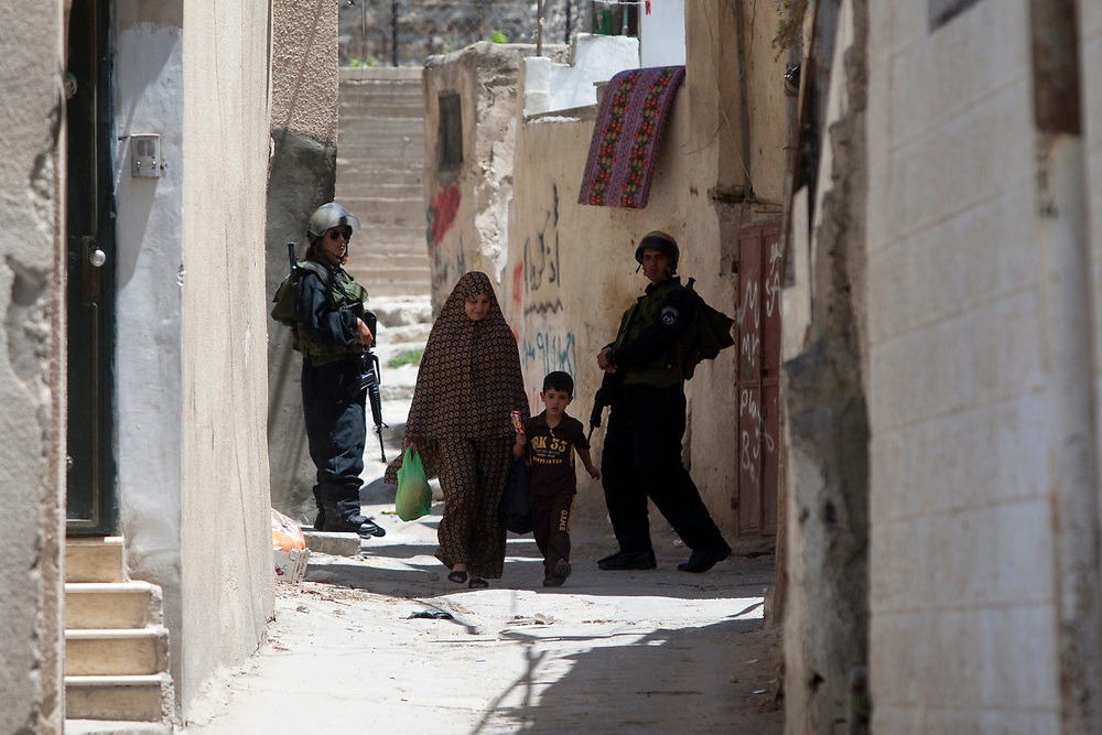 A Palestinian woman and her child pass between Israeli border policemen in an alley in the east Jerusalem neighborhood of Silwan, during a visit by the Israeli parliament committee for the children's rights to houses of Jewish families residing in a mostly Arab area, July 6, 2010.