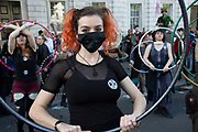 Extinction Rebellion climate change activists with hula hoops as sites around Westminster are blocked on 8th October 2019 in London, England, United Kingdom. Extinction Rebellion is a climate group started in 2018 and has gained a huge following of people committed to peaceful protests. These protests are highlighting that the government is not doing enough to avoid catastrophic climate change and to demand the government take radical action to save the planet.