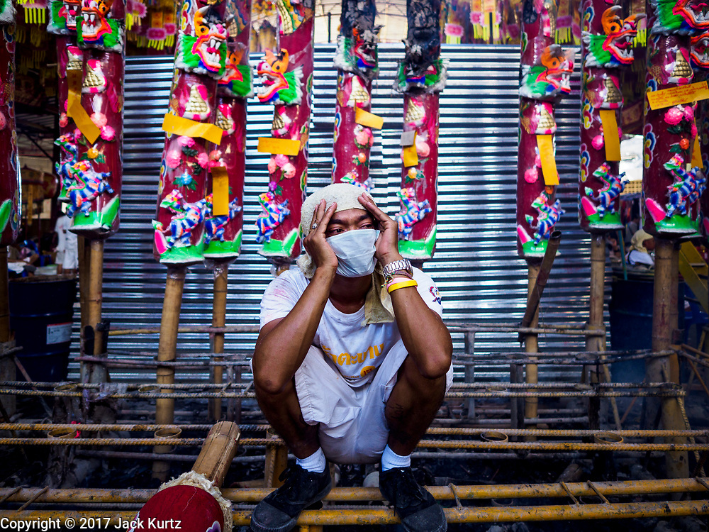 """20 OCTOBER 2017 - BANGKOK, THAILAND: A volunteer waits to help devotees at Chao Zhou Shi Kong Shrine in Bangkok's Chinatown on the first day of the """"Vegetarian Festival"""", what Thais call the Taoist Nine Emperor Gods Festival, in the Chinatown neighborhood of Bangkok, Thailand. It is a nine-day Taoist celebration beginning on the eve of 9th lunar month of the Chinese calendar. For nine days people participating in the festival wear only white and don't eat meat, poultry, seafood, and dairy products. The vegetarian festival is celebrated throughout Thailand, but especially in Phuket and Bangkok, cities with large ethnic Chinese communities.       PHOTO BY JACK KURTZ"""