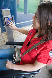 Young woman with cerebral palsy with her hand on a disability access door button,