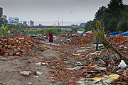A Nepalese woman walks through the remains of United Nations Park, Paurakhi Basti, next to the Bagmati River in the centre of Kathmandu, Nepal.  This used to be a slum area housing many Nepalese people. The government forces arrived in the middle of the night and used tear gas to displace the residents before demolishing their homes.
