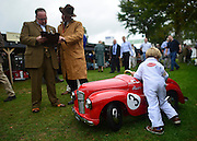 © Licensed to London News Pictures. 13/09/2013. Chichester, UK Harry Dark aged 4, from Oxfordshire, pushes his pedal car after it was checked for suitability to be in the Paddock. It passed.  People enjoy the atmosphere at the 2013 Goodwood Revival. The event recreates the glorious days of motor racing and participants are encouraged to dress in period dress. The revival is the only event of its kind to be staged entirely in the nostalgic time capsule of the 1940s, 50s and 60s Photo credit : Stephen Simpson/LNP.
