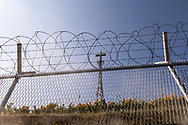 A cross viewed through razor wire and fencing at the Dora Observatory, the northernmost observatory in the Western section of the DMZ in South Korea.