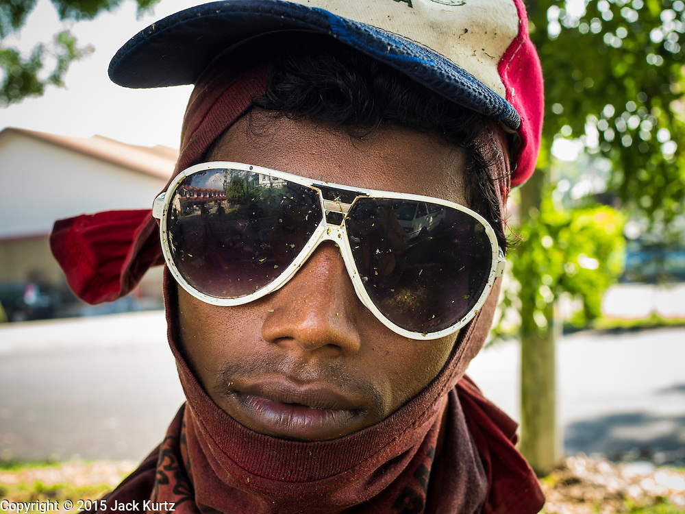 03 JUNE 2015 - KULAI, JOHORE, MALAYSIA: A Rohingya refugee who works as a street cleaner in a middle class neighborhood in Kulai, Malaysia. He said he is paid about 40 Malaysian Ringgit per day (roughly $11 US) to cut the grass in public spaces and keep sewer lines open. He came to Malaysia as refugee, this menial work is the only work he can find. The UN says the Rohingya, a Muslim minority in western Myanmar, are the most persecuted ethnic minority in the world. The government of Myanmar insists the Rohingya are illegal immigrants from Bangladesh and has refused to grant them citizenship. Most of the Rohingya in Myanmar have been confined to Internal Displaced Persons camp in Rakhine state, bordering Bangladesh. Thousands of Rohingya have fled Myanmar and settled in Malaysia. Most fled on small fishing trawlers. There are about 1,500 Rohingya in the town of Kulai, in the Malaysian state of Johore. Only about 500 of them have been granted official refugee status by the UN High Commissioner for Refugees. The rest live under the radar, relying on gifts from their community and taking menial jobs to make ends meet. They face harassment from Malaysian police who, the Rohingya say, extort bribes from them.    PHOTO BY JACK KURTZ
