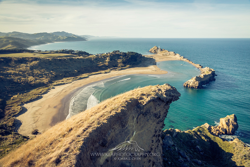 The end of Deliverance Cove Track scales up Castle Rock, yielding sweeping views of the Wairarapa coastline and the distant Castlepoint lighthouse.