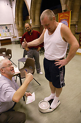 Man being weighed at slimmers club,