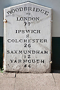 Old mile post marker with distances, Woodbridge, Suffolk, England