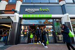 "© Licensed to London News Pictures. 07/03/2021. LONDON, UK.  Customers depart the new 2,500 sq ft Amazon Fresh store in Ealing, west London on its first weekend of opening. It is the first ""just walk out"" grocery store in the UK and the first outside the USA.  As a ""contactless"" shop, it is available to anyone signed up to Amazon and with the app on their smartphone.  In-store cameras and artificial intelligence monitor customers picking up items who simply walk out and billing takes place later automatically.  Photo credit: Stephen Chung/LNP"