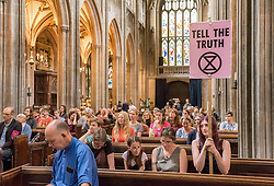© Licensed to London News Pictures. 19/07/2019; Bristol, UK. Extinction Rebellion Summer Uprising 2019. Extinction Rebellion event in St Mary Redcliffe church on the last day of the week's protest with readings from the Bible's Book of Revelation by the Reverend Dan Tyndall Vicar of St Mary Redcliffe, and other clergy and members of Extinction Rebellion. Extinction Rebellion are holding a five-day 'occupation' of Bristol, by occupying Bristol Bridge in the city centre and traffic has to be diverted and carrying out other events. As part of a country-wide rebellion called Summer Uprising, followers will be holding protests in five cities across the UK including Bristol on the theme of water and rising sea levels, which is the group's focus for the South West. The campaign wants the Government to change its recently-set target for zero carbon emissions from 2050 to 2025. Photo credit: Simon Chapman/LNP.