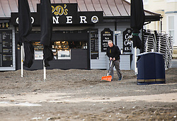 © London News Pictures. 22/10/2017. Aberystwyth,UK. A seafront cafe owner starts the long job of clearing tons of sand from in front of his  cabin on the promenade. After two days of winds, the tail end of storm Brian is still battering the seafront and promenade in Aberystwyth on the Cardigan Bay coast of west wales. Photo credit: Keith Morris/LNP