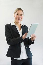 Portrait of businesswoman in black suit using digital tablet, smiling