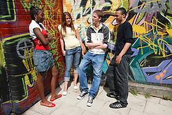 Teenage group standing by mural.