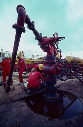Stock photo of an oil field frac operation in Texas. Connecting pipe to wellhead.
