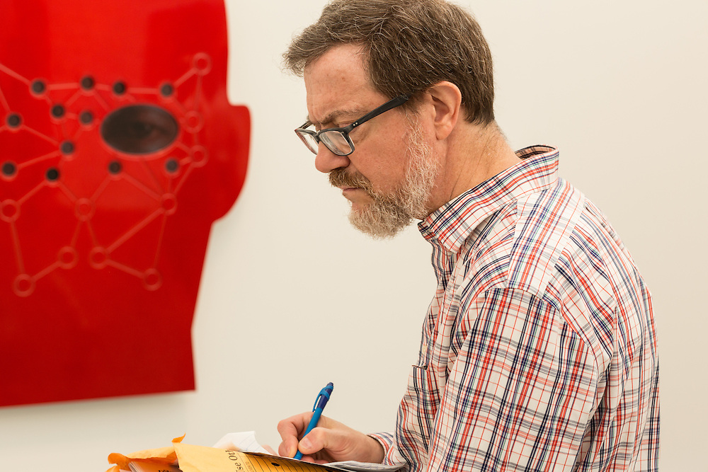 """A visitor takes notes in the booth of the Lehmann Maupin Gallery. Behind him is a detail of """"ePRO"""" by Tony Oursler."""