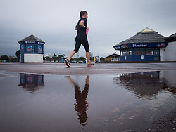 © Licensed to London News Pictures. 29/09/2016. Portsmouth, Hampshire, UK.  A runner passes puddle by the Bluereef Aquarium in Southsea this morning, 29th September 2016. Wet and windy weather hits the south coast this morning, following days of warm sunny weather. Photo credit: Rob Arnold/LNP