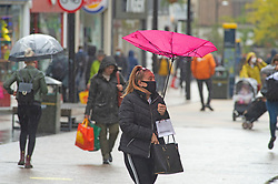 ©Licensed to London News Pictures 13/10/2020  <br /> Bromley, UK. A young lady wearing a protective face mask trying to keep control of her umbrella in the wind and rain. Autumnal wet weather this afternoon for shoppers in Bromley High Street, Bromley, South East London. Photo credit:Grant Falvey/LNP