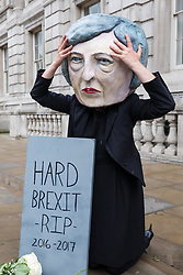 © Licensed to London News Pictures. 09/06/2017. London, UK. Campaigners from the organisation Avaaz pose outside the Cabinet Office with a Theresa May head and a gravestone mourning the 'death of hard Brexit'. Prime Minister Theresa May failed to secure a parliamentary majority in the 8 June 2017 General Election, which she claimed was needed for effective negotiations for Britain's exit from the European Union.  Photo credit: Rob Pinney/LNP