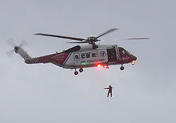 © Licensed to London News Pictures. 18/12/2018. Falmouth, UK. A member of a search and rescue hangs from a coastguard helicopter flying over Russian cargo ship Kuzuma Minin, run aground on the reef off Gyllyngvase beach in Falmouth Bay in the early hours this morning. The Falmouth lifeboat and the Coastguard helicopter are involved in the major incident.  Photo credit: Mark Hemsworth/LNP