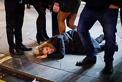 © Licensed to London News Pictures. 01/01/2017. London, UK. An intoxicated reveller lies on pavement as people celebrate the New Year in central London during the first hours of 2017 on January 1. Photo credit: Tolga Akmen/LNP
