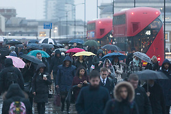"© Licensed to London News Pictures. 15/01/2018. London, UK. Commuters cross London Bridge on their way to work during wet and windy weather this morning. Today is known as ""Blue Monday"", the gloomiest and most depressing day of the year.. Photo credit: Vickie Flores/LNP"