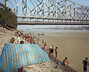 It is morning in Kolkata (Calcutta), West Bengal, India and on the West bank of the Hooghly River the banks are busy with bathing men with the Howrah Bridge beyond. The bathers are either drying themselves after washing in the river, or are undressing to do so. It is a scene of inner-peace, a tranquillity surrounded by the chaotic pace of Indian life in this city. The engineering of the bridge stretches across the water towards the city beyond. The bridge is one of three on the Hooghly River and is a famous symbol of Kolkata and West Bengal. Bearing the daily weight of approximately 150,000 vehicles and 4,000,000 pedestrians. It is one of the longest bridges of its type in the world. The Hooghly River is an approximately 260 km long distributary of the Ganges River.