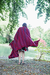 Woman wrapped in blanket at lakeshore in the English Garden, Munich, Germany