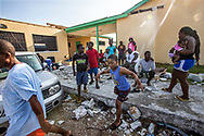 A child runs to get water after at a school-turned storm shelter in Marsh Harbour on Abaco Island on Saturday, September 7, 2019. Central Abaco Primary school has been housing more than 200 people left homeless by Hurricane Dorian.