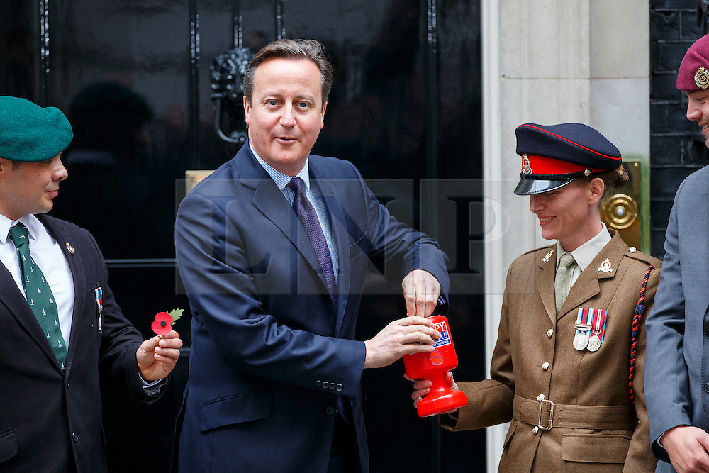 © Licensed to London News Pictures. 22/10/2015. London, UK. Prime Minister David Cameron gives a £10 note to buy a Royal British Legion poppy and meets current and former servicemen and women in Downing Street, London on Thursday, 22 October 2015. Photo credit: Tolga Akmen/LNP