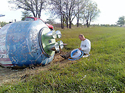 The Cement Mixer Space Capsule <br /> <br /> Along a lonely stretch of road between the small villages of Talala and Winganon in the US state of Oklahoma, lies what appears to be an abandoned space capsule. The letterings 'NASA' and 'United States of America' along with the flag is clearly visible on its side. However, it doesn't take long to realize that the fallen spacecraft is actually a cement mixer.<br /> The landmark came into being by a happy accident when a concrete-filled cement mixer truck, which was on its way to help build the bridge over Oologah Lake, had rolled over here in 1959. By the time a tow truck arrived to haul the cement truck away, all of the cement had hardened inside the mixer. Unable to handle the extra weight, the crew decided to haul only the truck and come back for the detached mixer later, which never happened. Eventually the locals discovered the relic, and the mixer became an easy target for anyone with spray paint.<br /> For the last fifty years, graffiti artists have poured untold gallons of paint over the mixer, sending messages to their friends, or just showing. In September 2011, local artists Barry and Heather Thomas decided to turn it into a space capsule to celebrate the fifth anniversary of their wedding. The couple attached canning lids, garden hose, broken reflectors and other household items to the mixer to make the transformation look as real as possible. Before the latest incarnation the mixer was painted in a patriotic stars-and-stripes motif.<br /> The Winganon Space Capsule is now a popular attraction. People driving along Winganon Road get down from their cars to pose near it and take pictures.<br /> Heather Thomas hopes the new paint job would discourage kids to paint it over with graffiti. It has definitely survived, till now, although the thrusters at the bottom are gone.<br /> ©Exclusivepix Media