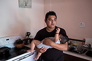 Carlos Rueda Cruz, 28, holds his 8-month-old son Santiago at his home in Sacramento, Calif., Monday, Sept. 10, 2018. Cruz, an undocumented immigrant from México, was threatened with deportation by U.S. Immigration and Customs Enforcement if he refused to give the agency names of other undocumented immigrants living among his community. (Joel Angel Juárez / The Intercept)